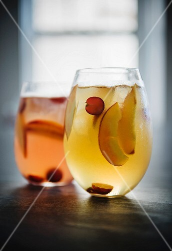 Two glasses of red and white sangria with fruit