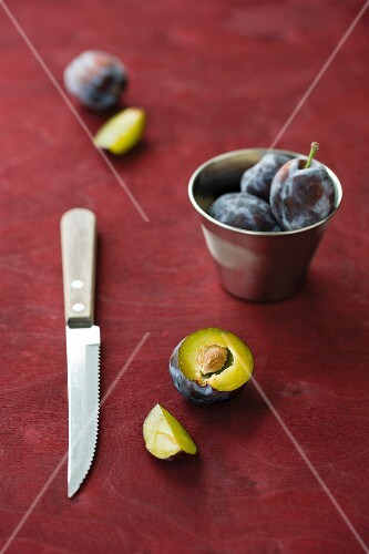 Damsons with a metal cup and a knife