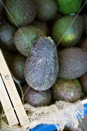 A crate of avocados at a market