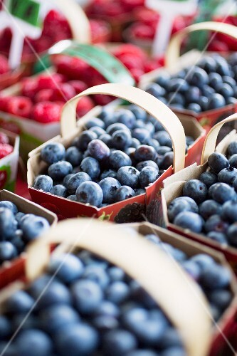 Blueberries and raspberries in cardboard punnets at a market