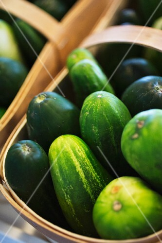 Cucumbers in a wooden basket at a market