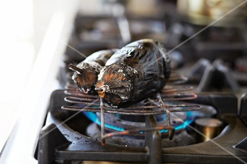 Charred aubergine on a gas stove
