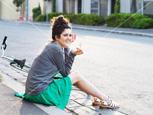 A young woman with a bicycle sitting on the pavement eating ice cream