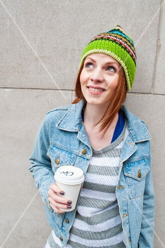 A young woman with a takeaway coffee leaning against a wall
