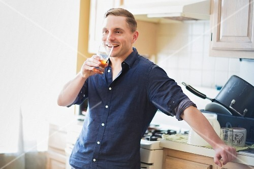 A man drinking a glass of homebrewed beer in a kitchen