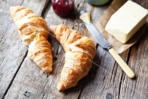 Freshly baked croissants with salted butter and raspberry jam
