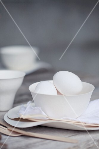 Eggs in a white porcelain bowl on a wooden table