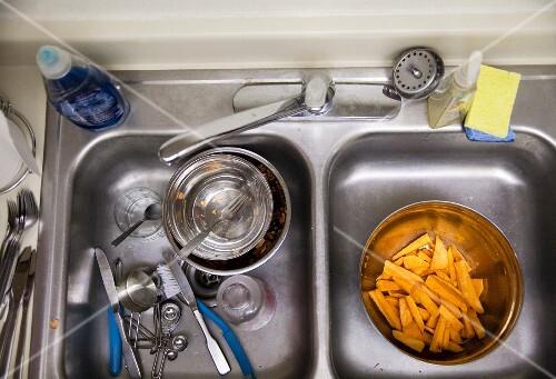 Doppelspülbecken mit geschnittenen Süßkartoffeln und schmutzigem Geschirr