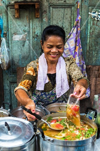 A woman selling Tom Yam (spicy-sour soup, Thailand)