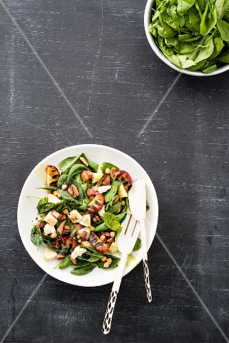 Spinach salad with chickpeas, gorgonzola, pecan nuts and grilled plums