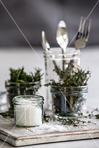 Salt, thyme, rosemary and cutlery in jars
