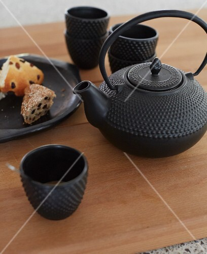 Black, cast iron tea service with Oriental teapot and plate of pastries
