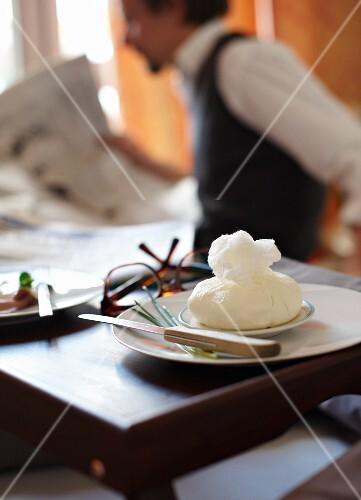 Homemade cream cheese in a muslin cloth for breakfast