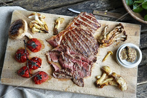 Grilled steak, mushrooms and tomatoes on a chopping board