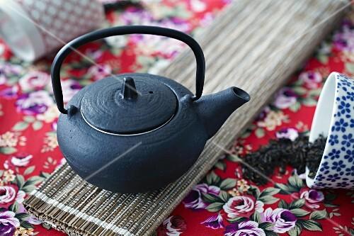A black oriental teapot seen from above