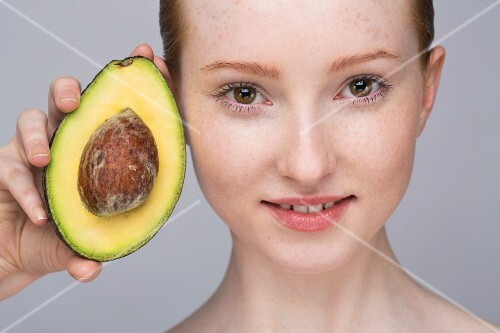 A portrait of a young woman holding an avocado half