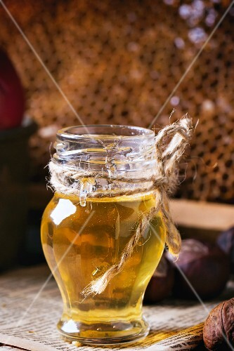 A jar of honey with honeycombs in the background