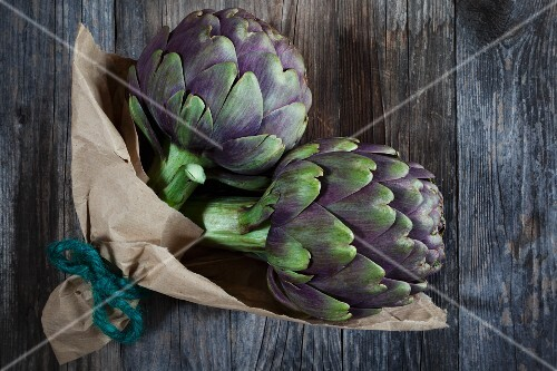 Two artichokes on a wooden table