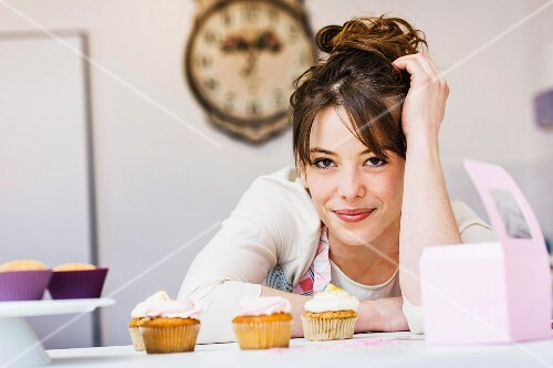 A woman in a kitchen with cupcakes