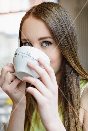 A young woman drinking a large cup of coffee