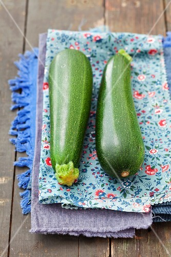 Two courgettes on a floral-patterned cloth