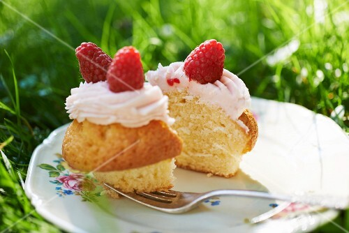 A cupcake topped with buttercream and raspberries