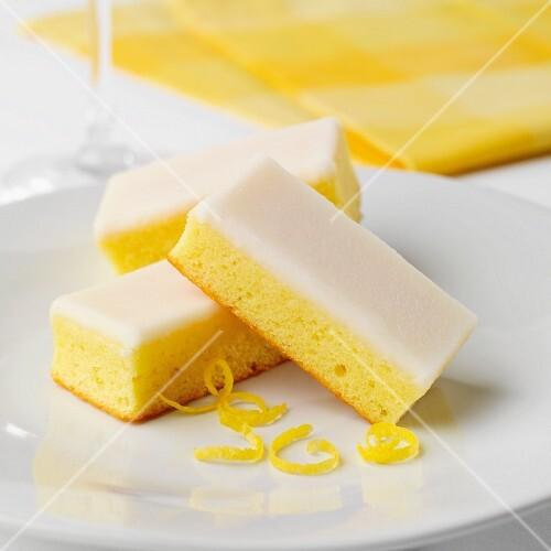 Three slices of lemon cake with icing sugar and lemon zest