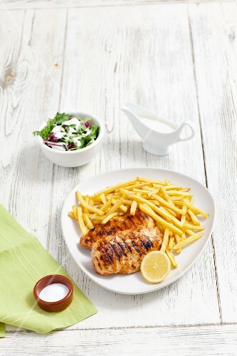 Grilled chicken breast with chips and salad