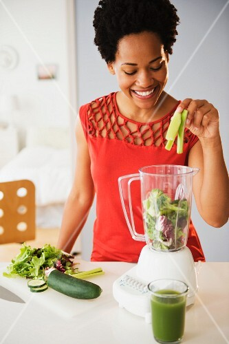 A young black woman placing ingredients for green smoothie into a blender