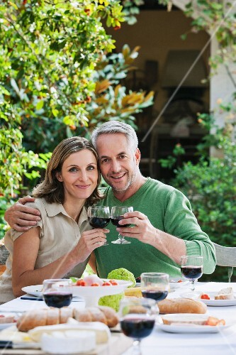 A couple eating together outdoors holding glasses of red wine