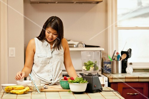 A young woman making green smoothies in a kitchen