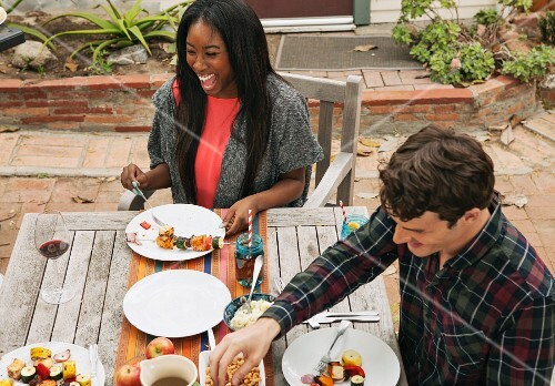 A couple at a garden table with grilled vegetable skewers
