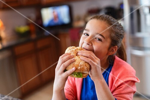 A girl in a kitchen biting into a large sandwich
