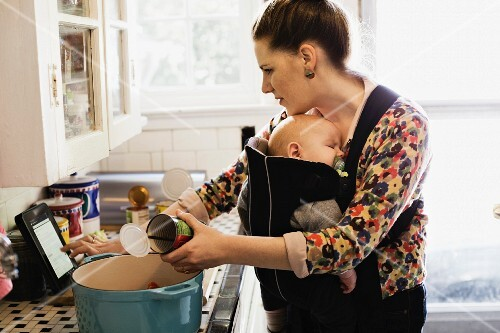 A young woman with a baby in a sling making food according to a recipe on a tablet PC