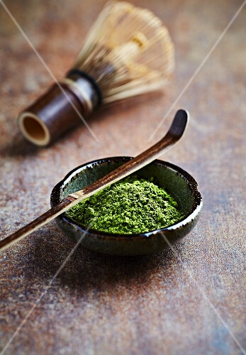 Matcha tea powder with a bamboo whisk