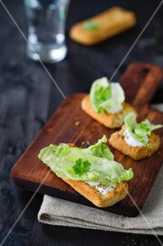Bruschetta topped with yoghurt cream and iceberg lettuce
