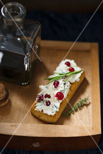 Bruschetta topped with rosemary and thyme cream cheese and redcurrants