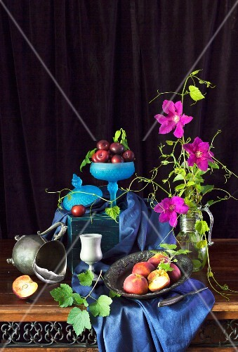 An arrangement of peaches, plums and purple clematis