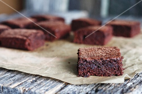 Brownies on a piece of baking paper on a wooden table