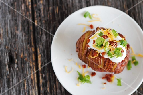 A Hasselback potato with a topping made from crème fraîche, spring onions, bacon and cheddar