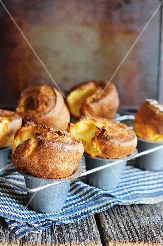 Cheese soufflés in a baking tin on a tea towel on a wooden table