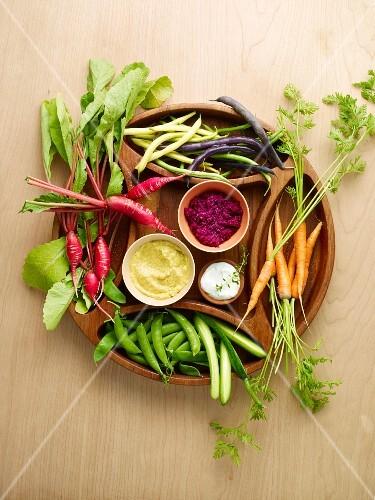 Fresh garden vegetables with dips on a wooden platter