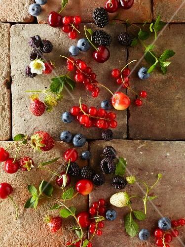 Fresh berries and cherries on a tiled floor