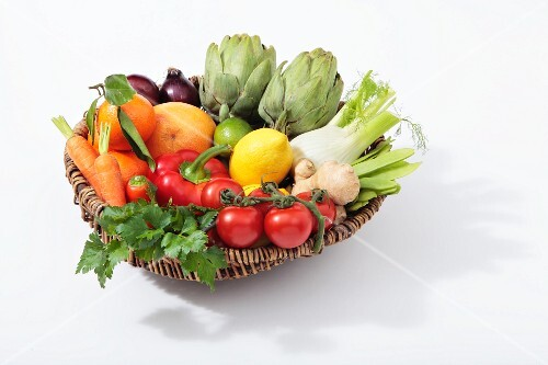 A basket of vegetables with citrus fruits and ginger