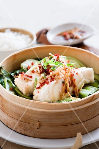 Steamed fish on a bed of bok choy with ginger and chilli