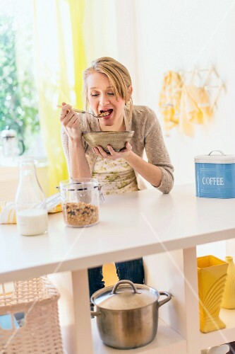 A blonde woman eating muesli in a kitchen