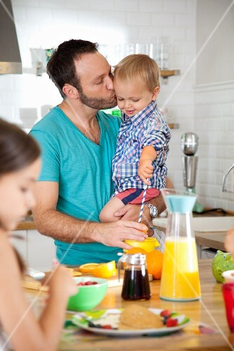 A man having breakfast with his son and daughter