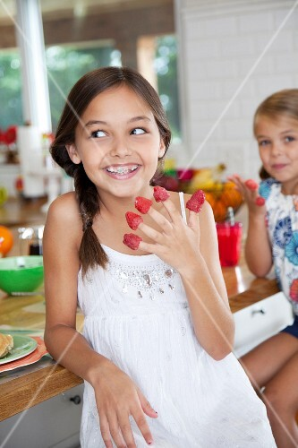 Two sisters with raspberries on their fingers in a kitchen