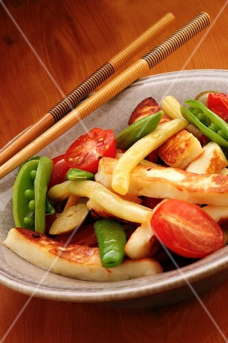 Fried vegetables in a bowl with chopsticks