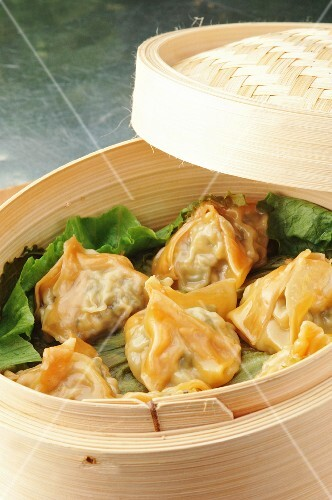 Won tons filled with Thai chicken on a bed of lettuce in a steamer basket